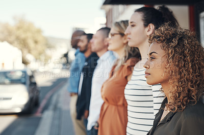 Buy stock photo Shot of a group of people standing in a line in the city