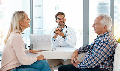 Buy stock photo Cropped shot of a handsome male doctor consulting with a couple in his office
