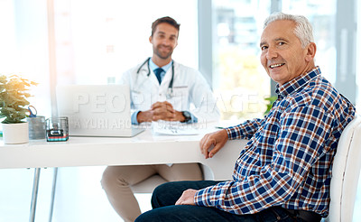 Buy stock photo Cropped portrait of a handsome male doctor consulting with a patient at his desk
