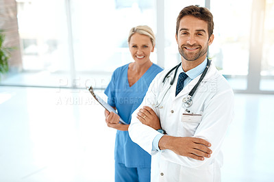 Buy stock photo Cropped portrait of two happy healthcare practitioners posing together in a hospital