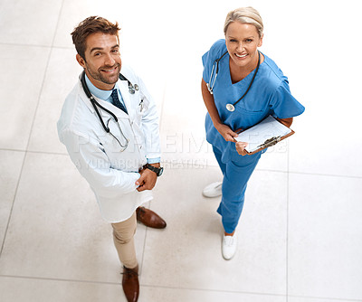 Buy stock photo High angle portrait of two happy healthcare practitioners posing together in a hospital