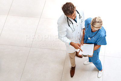 Buy stock photo High angle shot of two healthcare practitioners looking over documents in the hospital