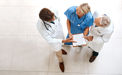 Buy stock photo High angle shot of a team of doctors brainstorming over a patient's file in the hospital foyer