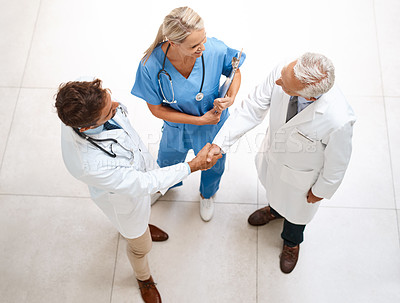 Buy stock photo High angle shot of a team of doctors shaking hands in the hospital