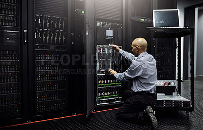 Buy stock photo Rearview shot of an IT technician repairing a computer in a data center