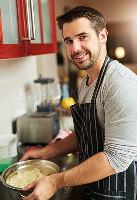 Buy stock photo Shot of a young man cooking in the kitchen