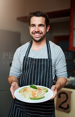 Buy stock photo Cropped portrait of a handsome young man serving food in the kitchen at home