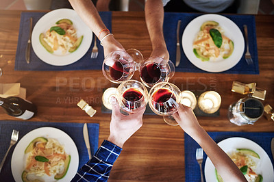 Buy stock photo High angle shot of a group of unrecognizable people toasting at the dining room table at home