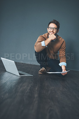 Buy stock photo Studio shot of a young businessman working on a laptop against a grey background
