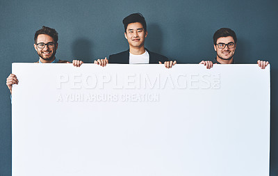 Buy stock photo Studio shot of businesspeople holding up a blank sign against a grey background