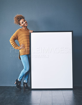 Buy stock photo Studio shot of a young woman posing with a blank sign against a grey background