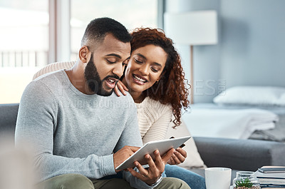Buy stock photo Shot of a young couple using a credit card and digital tablet at home