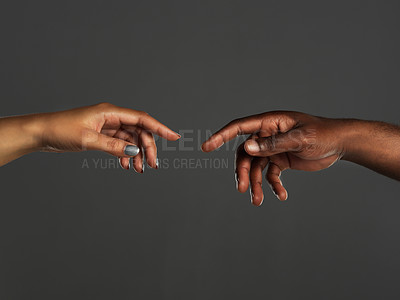 Buy stock photo Studio shot of two unrecognizable people reaching out their hands towards each other against a grey background