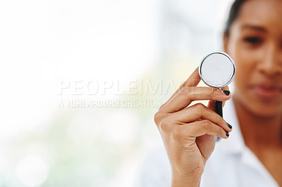 Buy stock photo Portrait of a young doctor holding up a stethoscope in a hospital