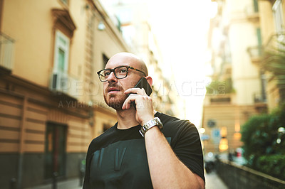 Buy stock photo Shot of a young man using a smartphone in the city