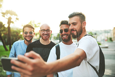 Buy stock photo Shot of a group of friends taking selfies together in the city