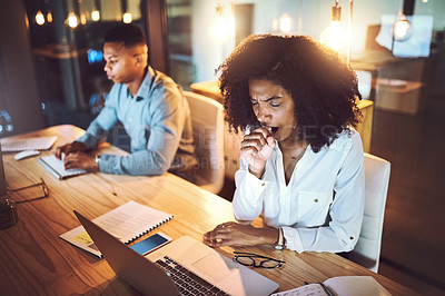 Buy stock photo Shot of a young businesswoman yawning while working alongside her colleague in an office at night