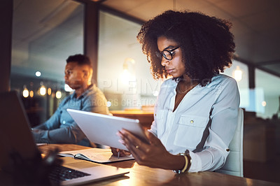 Buy stock photo Shot of a young businesswoman using a digital tablet while working alongside her colleague in an office at night
