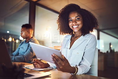 Buy stock photo Portrait of a young businesswoman using a digital tablet while working alongside her colleague in an office at night