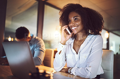 Buy stock photo Shot of a young businesswoman talking on a cellphone while working alongside her colleague in an office at night