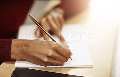 Buy stock photo Closeup shot of a university student writing notes in his book