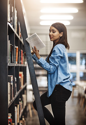 Buy stock photo Shot of a university student using a ladder to reach a book in the library at campus