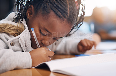 Buy stock photo Cropped shot of an elementary school girl doing school work in the classroom