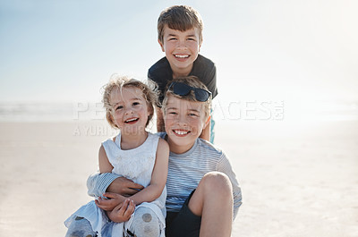 Buy stock photo Portrait of three happy young siblings enjoying a day at the beach