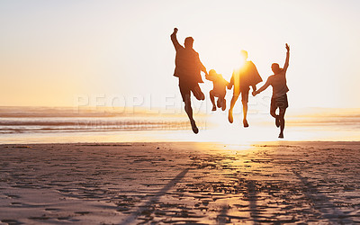 Buy stock photo Rearview shot of a happy young family jumping for joy at the beach