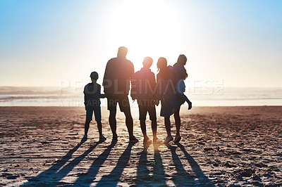 Buy stock photo Rearview shot of a happy young family bonding on the beach at sunset