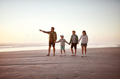 Buy stock photo Shot of a happy young family going for a walk together along the beach