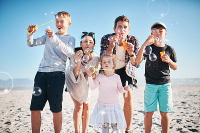 Buy stock photo Shot of a happy young family blowing bubbles together at the beach