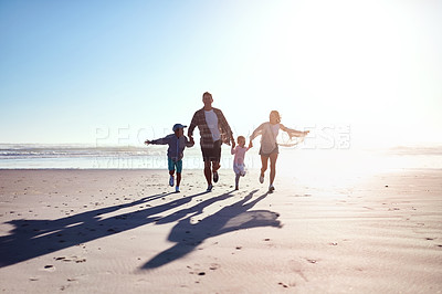 Buy stock photo Shot of a happy young family of four running together on the beach