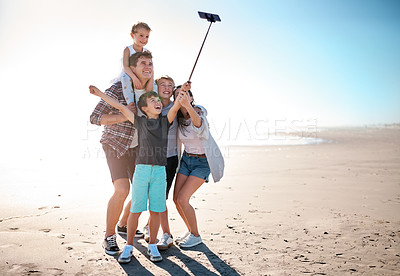 Buy stock photo Shot of a happy young family taking selfies together at the beach