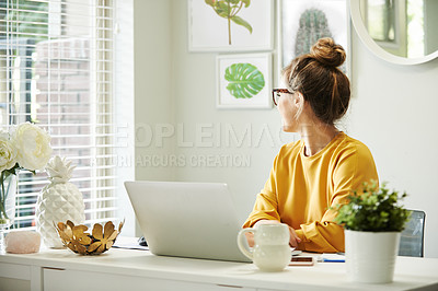 Buy stock photo Shot of a young woman looking thoughtfully out the window of her home office