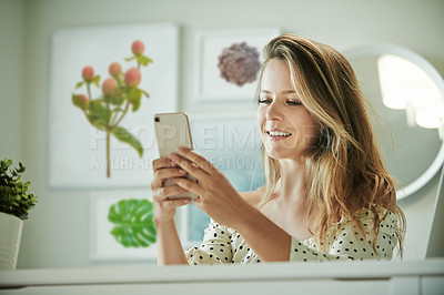 Buy stock photo Shot of a young woman using a mobile phone while working from home