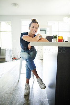 Buy stock photo Shot of a young woman using a laptop on the kitchen counter at home
