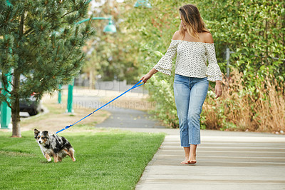 Buy stock photo Shot of a young woman walking her dog outdoors