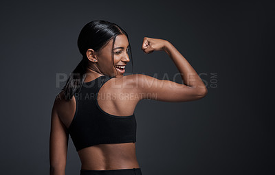 Buy stock photo Studio portrait of a young sportswoman flexing her bicep with her back turned to the camera against a gray background