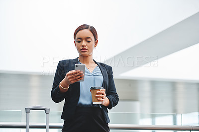 Buy stock photo Cropped shot of an attractive young businesswoman sending a text message while standing in the airport