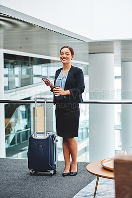 Buy stock photo Full length portrait of an attractive young businesswoman sending a text message while standing in the airport