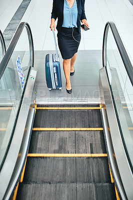 Buy stock photo High angle shot of an unrecognizable young businesswoman wheeling her luggage through the airport