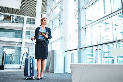 Buy stock photo Full length shot of an attractive young businesswoman using her tablet while walking through the airport