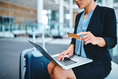 Buy stock photo Cropped shot of an unrecognizable young businesswoman using her laptop top shop online while sitting in the airport