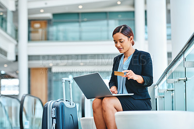 Buy stock photo Cropped shot of an attractive young businesswoman using her laptop to shop online while sitting in the airport