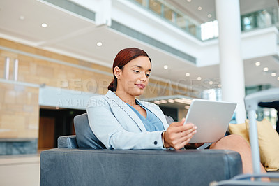 Buy stock photo Cropped shot of an attractive young businesswoman using her tablet while sitting in the airport