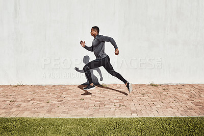 Buy stock photo Full length shot of a handsome and athletic young man running on a path through the park