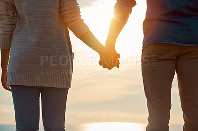 Buy stock photo Rearview shot of a young couple holding hands outdoors