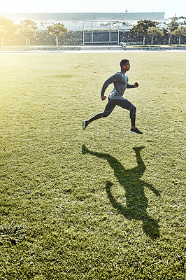 Buy stock photo Full length shot of a handsome and athletic young man running across an open field