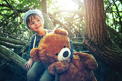 Buy stock photo Shot of a little boy playing with a teddybear outside